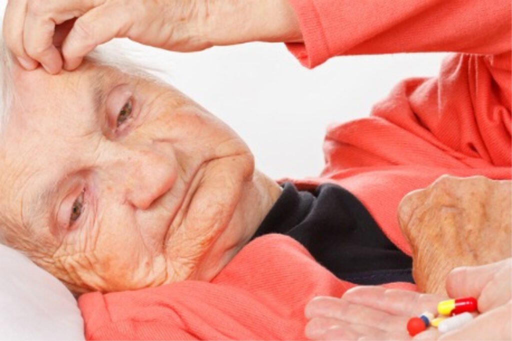 Caregiver giving medication to her senior patient